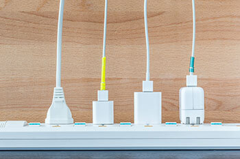 4 white modern plugs, on a outlet power strip
