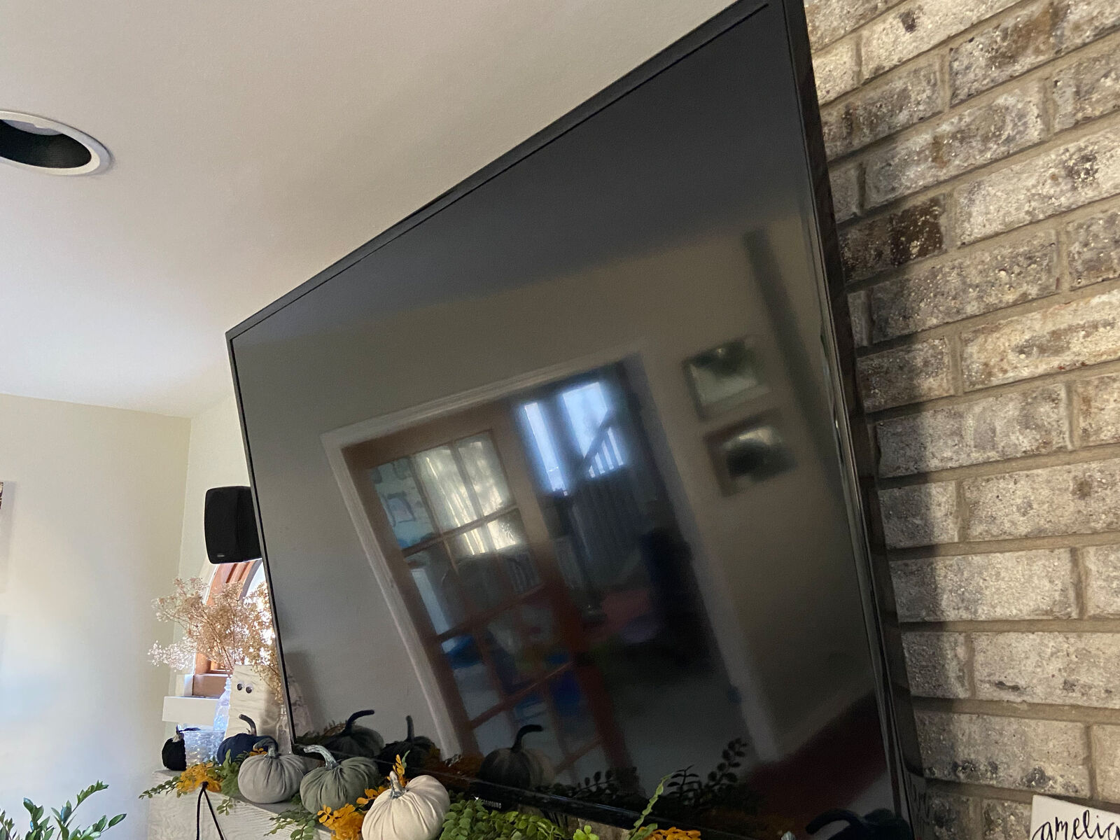 TV mounted to masonry above a fireplace