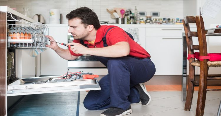 serviceman fixing dishwasher