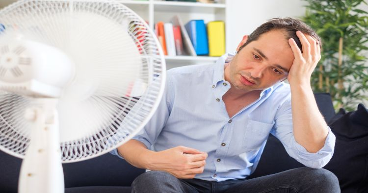 Man cooling off with broken AC