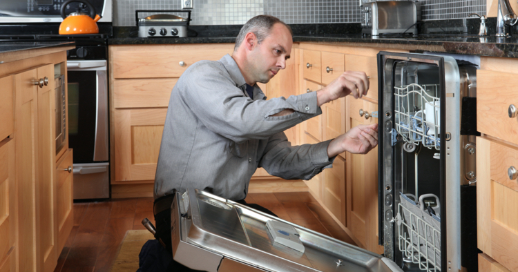 Worker fixing dishwasher