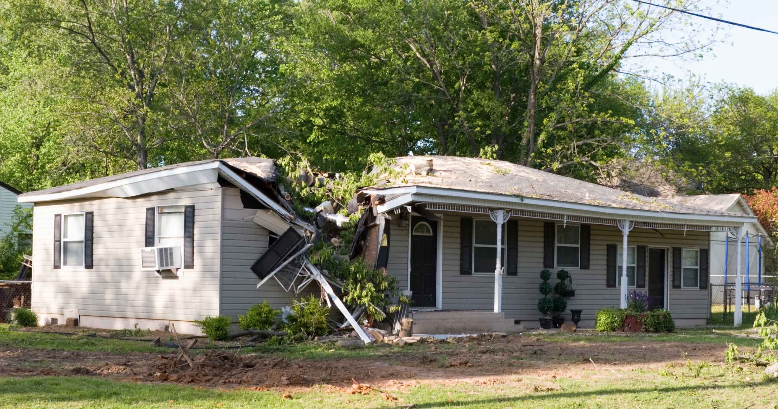 A damaged home after a large tree fell on it during a storm.