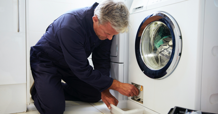 Man repairing washer and dryer