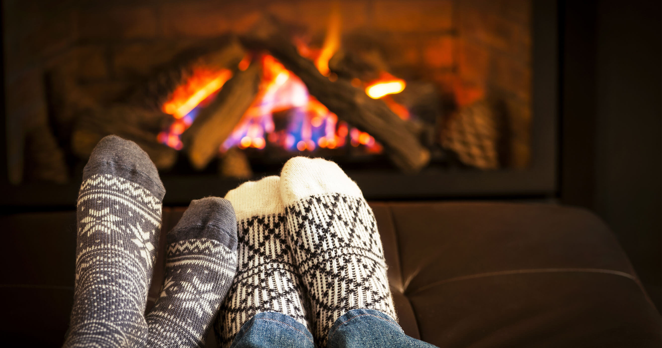 A couple putting their feet up by the warm fire.