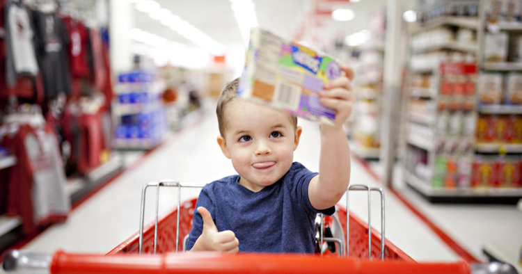 Little boy in shopping cart holding box