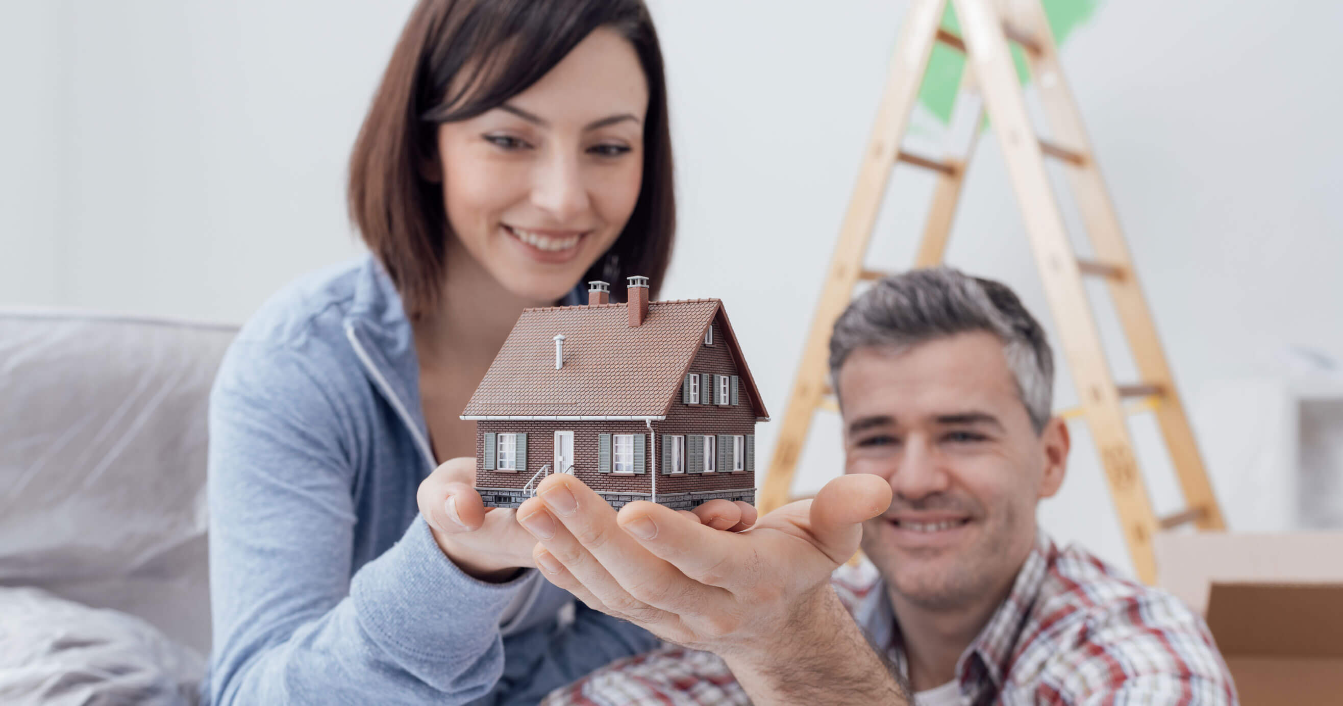 Couple holding model of a house