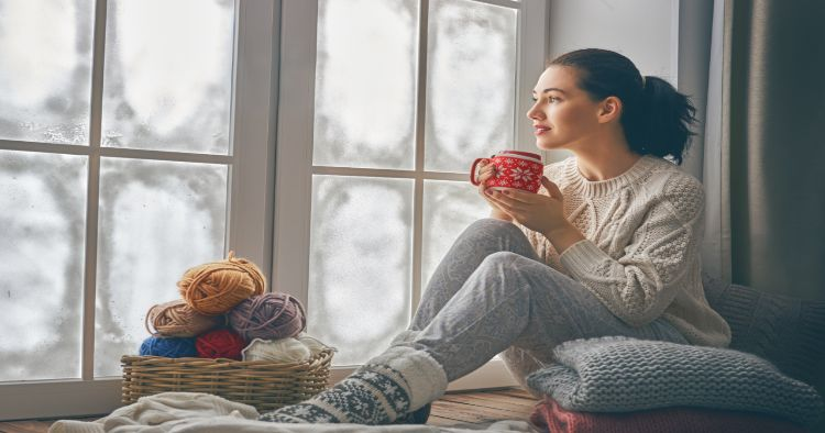 woman sitting in front of frosty window