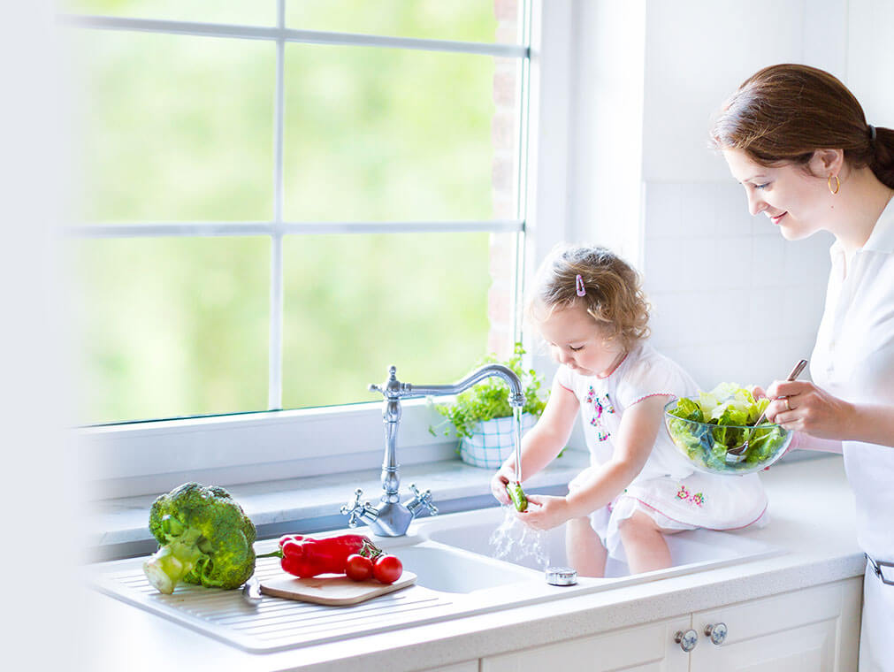 Baby and mother washing salad in sink