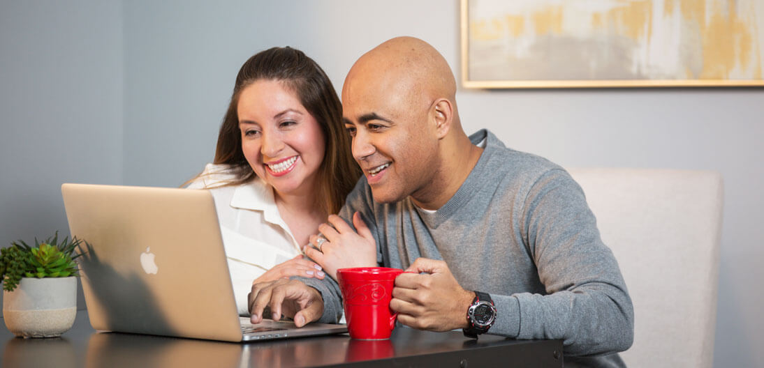 Couple looking at their computer in home office and smiling.