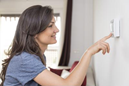 Woman turning on thermostat