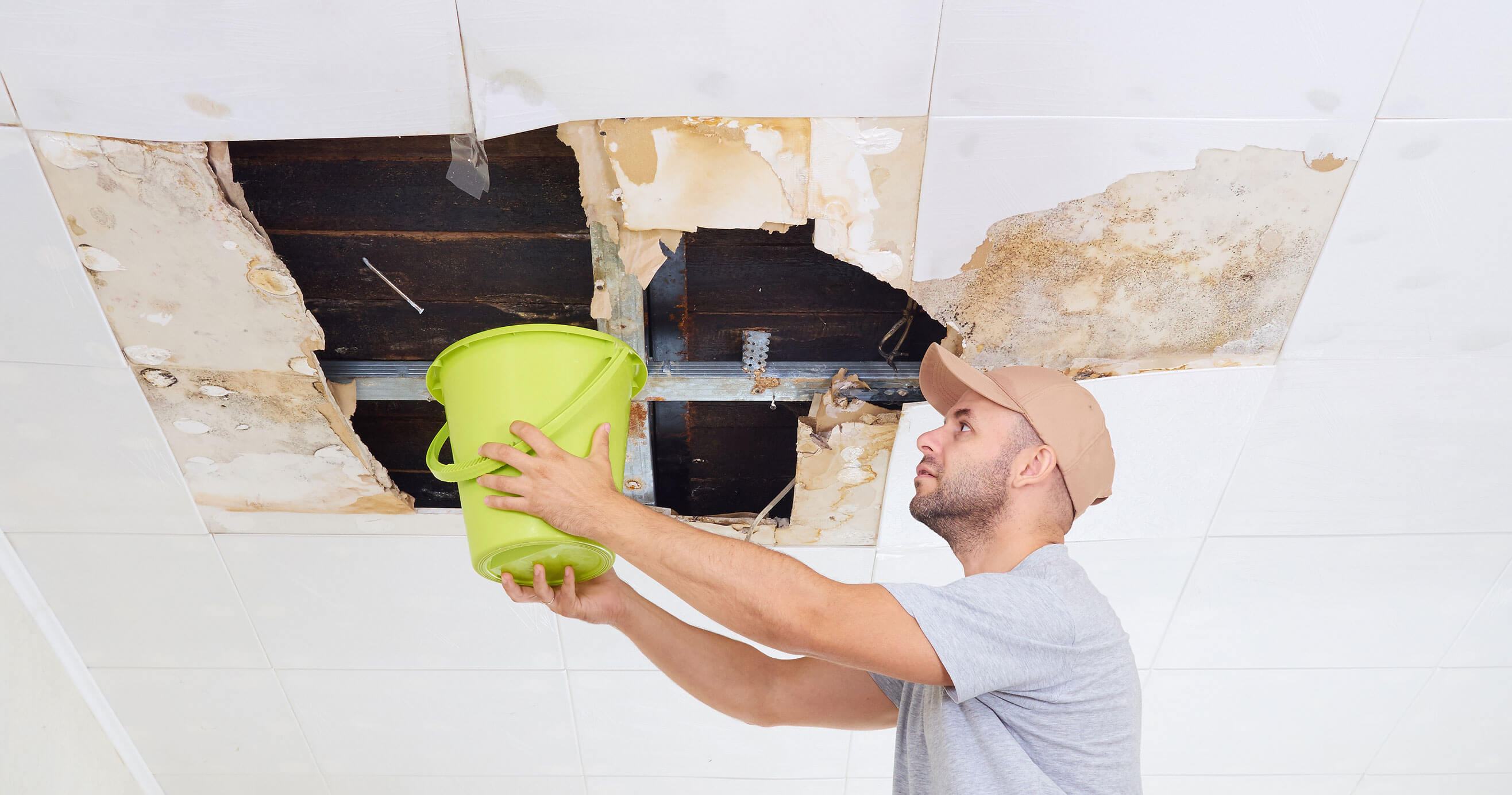 Man hold a bucket under a leak in ceiling