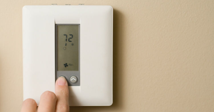 Person turning down temperature on thermostat