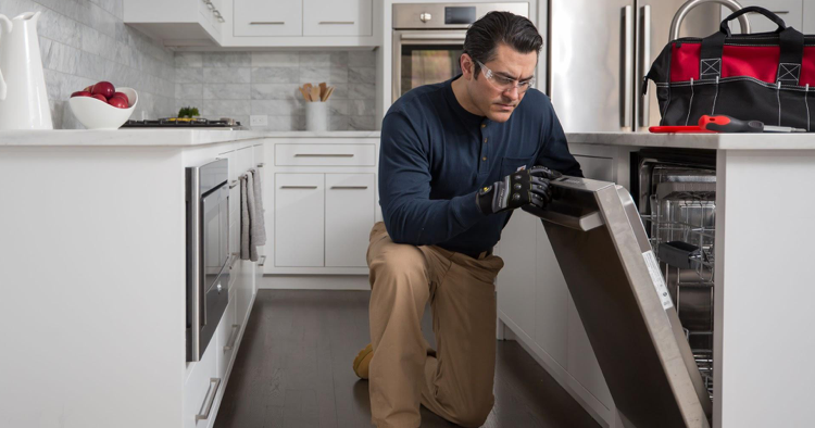 Professional technician working on fixing dishwasher