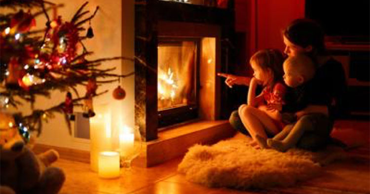 Mom and son in front of fire in the living room with Christmas tree