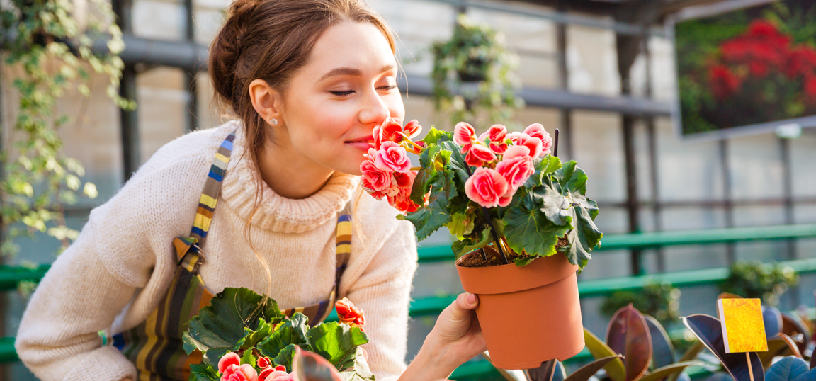 Woman smelling potted flowers