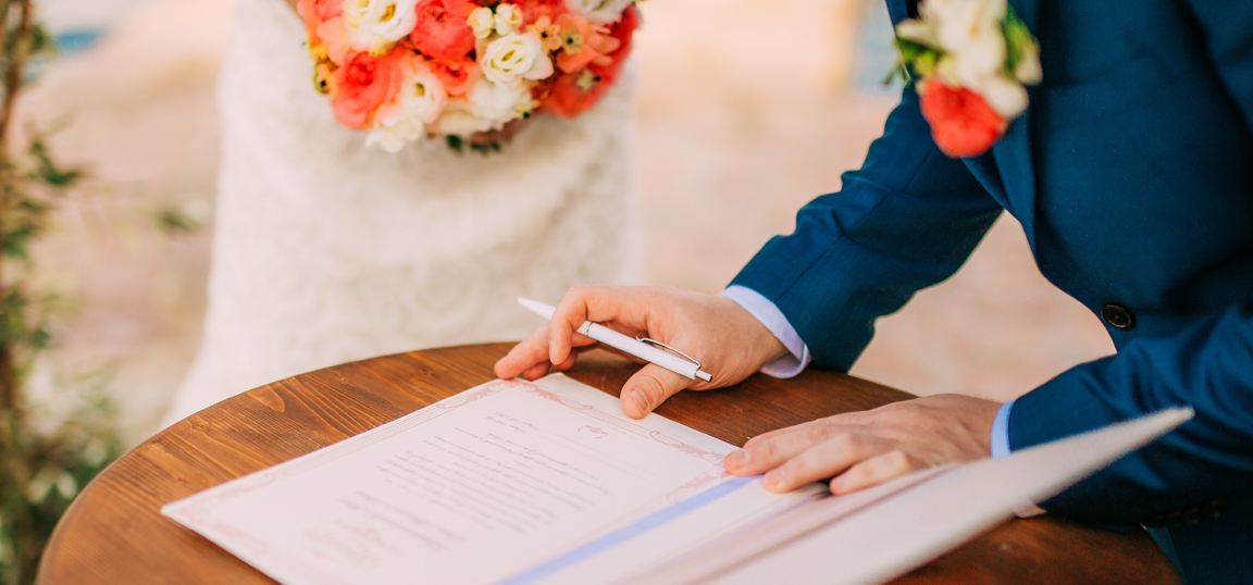 Man signing registry book at wedding
