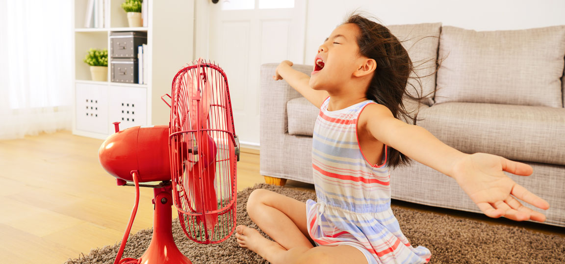 Little girl in striped dress in front of a red fan in home in summer