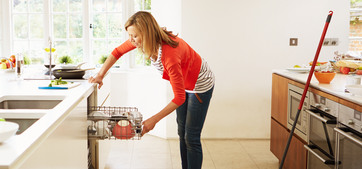 Women in red cardigan loading dishwasher in a clean kitchen