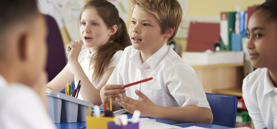 Young boy at school in a white shirt holding a red pencil sat next to a young girl with lots of stationery on the table