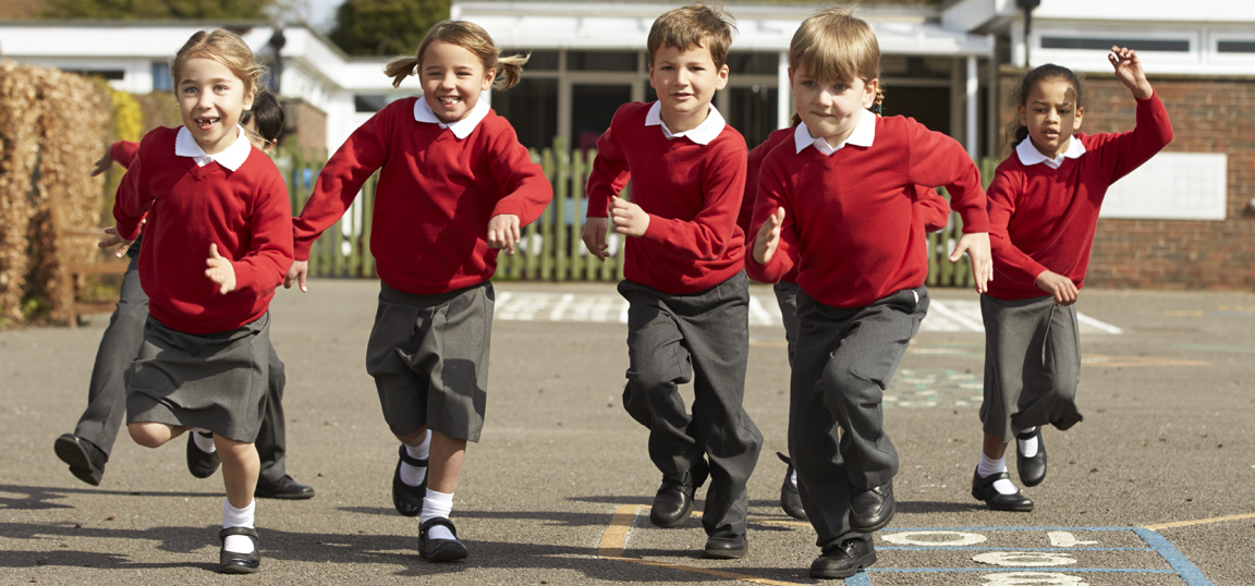 Children at school in their red uniforms running