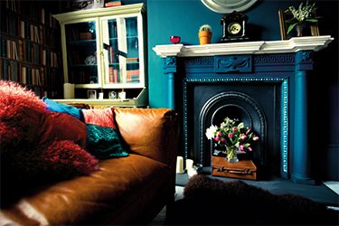 A tan leather sofa in a living room with a dark bluey fireplace and walls