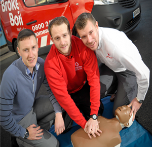 Engineers and staff with a CPR dummy beside HomeServe van