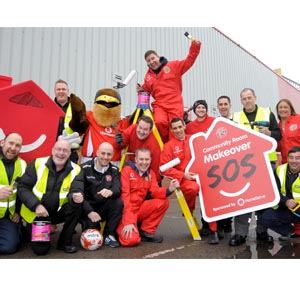 Group of people with decorating tools in red overalls with the HomeServe Mascot and Walsall Swift Mascot