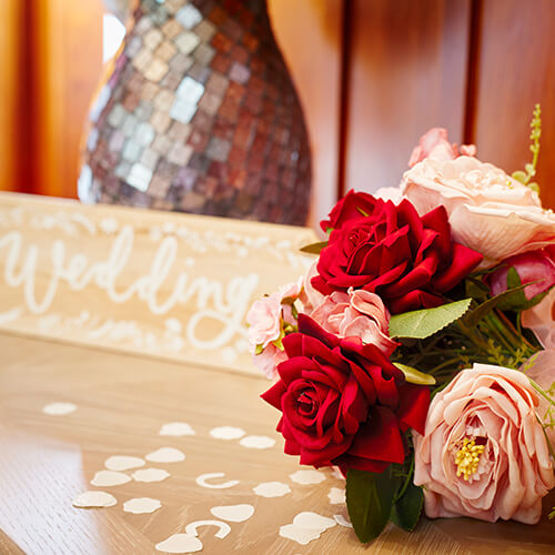 a bouquet of roses next to a wooden sign saying