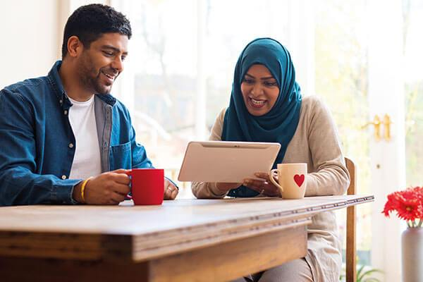 Young happy couple looking at laptop